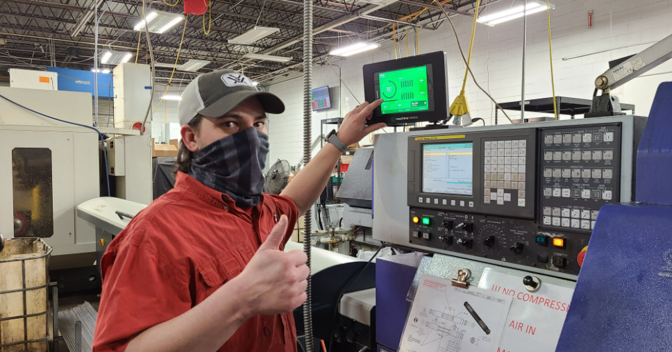 Operator Gives a Thumbs Up at a CNC Machine.