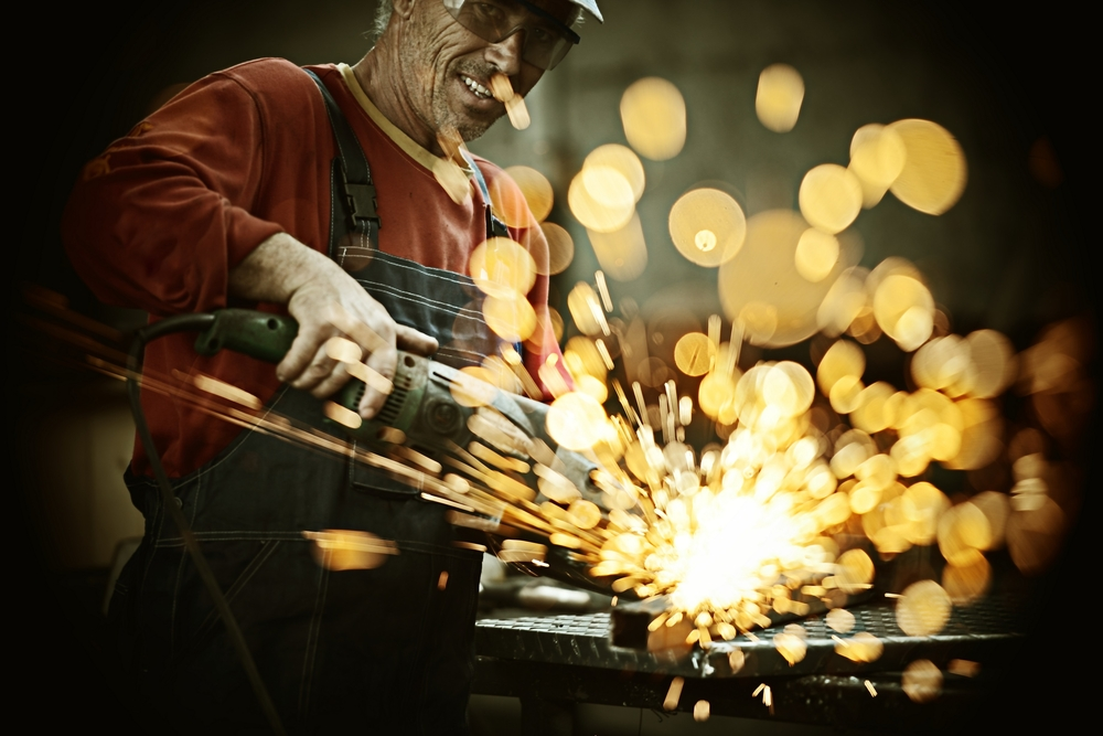 Industrial worker cutting and welding metal with many sharp sparks-1