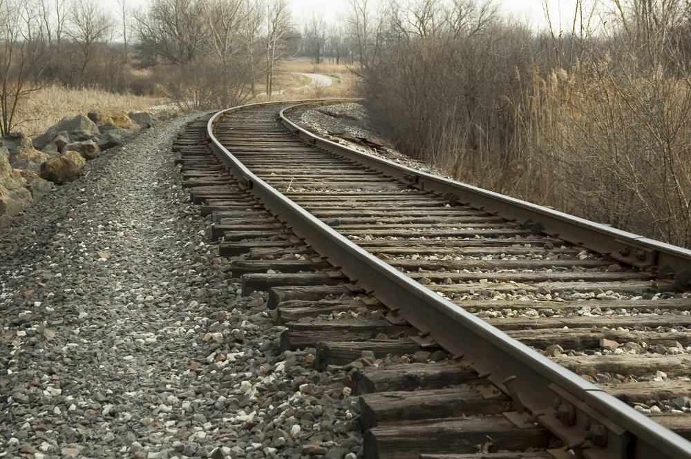 Railroad tracks curving in one direction, bike path in another