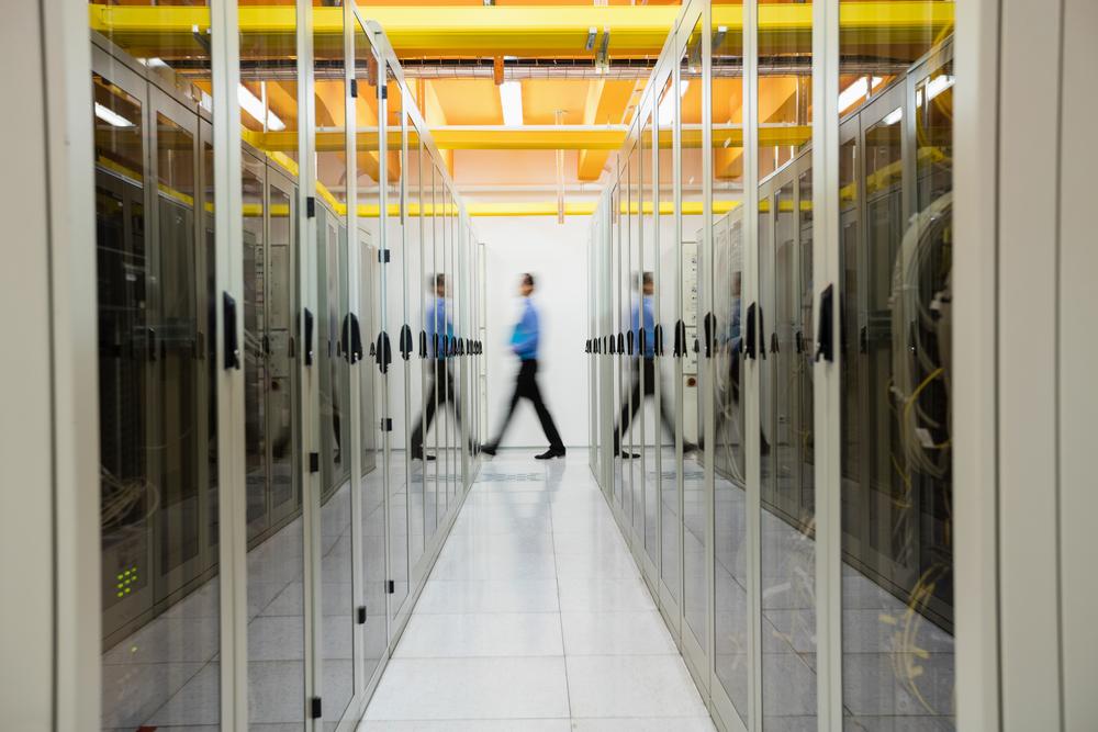 Technician walking in hallway of server room